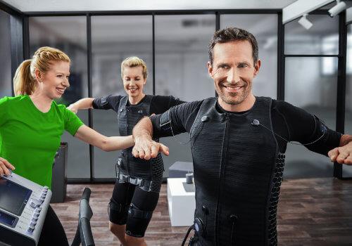 Zwei Kunden mit Trainerin beim EMS Training