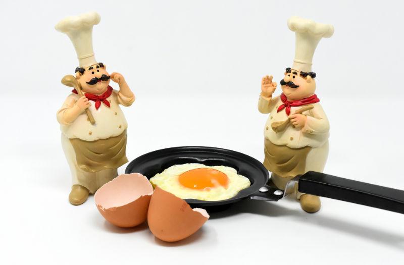 Pfanne mit Ei und Miniaturköche neben der Pfanne